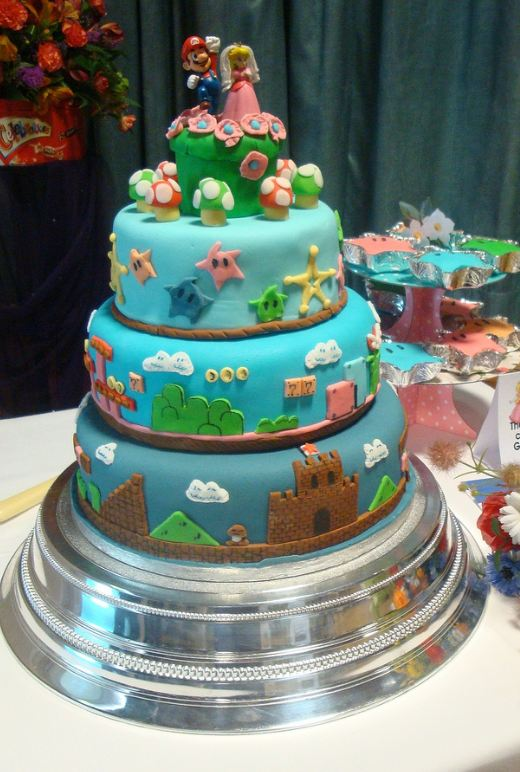 Three tier Super Mario theme wedding cake with Mario and Princess toppers.JPG