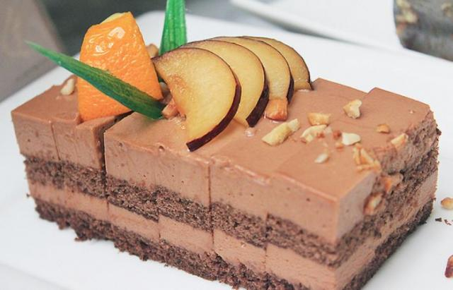 Chocolate cream cake with sliced apricot and sprinkled nuts on top.JPG
