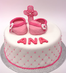 Chic baptism cake in white with pink dots and cross and shoes cake toppers in bright pink.PNG