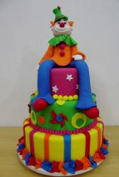 3 tier colorful cake with clown sitting on top.JPG