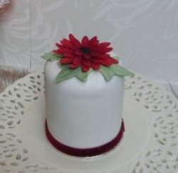 Christmas cake with big christmas flower as cake topper.PNG