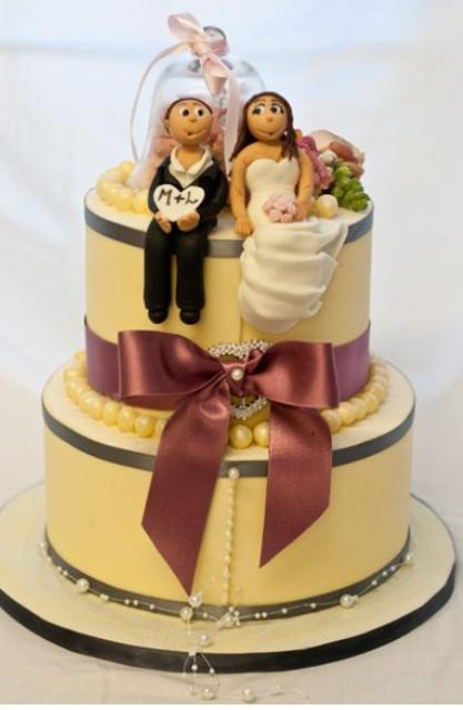 wedding cake with bow and bride and groom toppers in sitting position