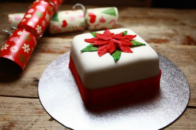 Mini white Christmas cake with red leaves on top.JPG