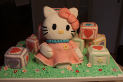Hello Kitty cakes sitting on the grass surrounding with cubes.PNG