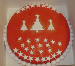 Red Christmas cake with white stars and balls.PNG