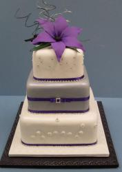 Tri-tier square wedding cake with rounded corners and purple flower on top.JPG