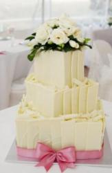 3 tier white chocolate wedding cake with white roses on top with pink ribbon around base.JPG