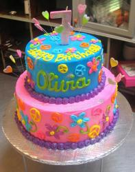 2 tier round birthday cake for 7-year-old girl in bright pink and blue with peace symbols and flowers.JPG