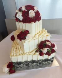Three tier white chocolate wedding cake with red and white roses.JPG