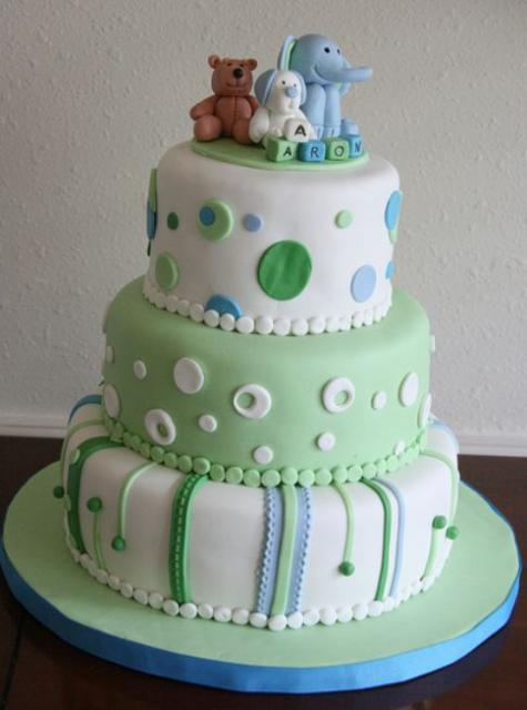 Three tier baby shower cake for boy with pokadots and baby elephant, puppy and bear on top and baby name spelled out in toy bloc