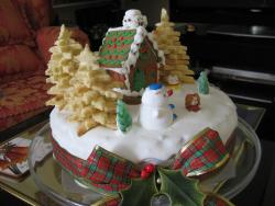 Round white Christmas cake with cookies as Christmas trees with cabin and snowman and bow.JPG