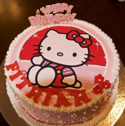 Red and pink Hello Kitty cakes with hello kitty print and small white and red flowers.PNG