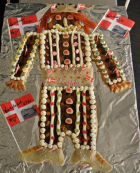 Viking danish kagemand with fancy cake decor with cake cream and candy and large danish birthday flags.PNG