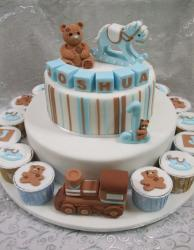 2 tier baby shower cake surrounded by cupcakes with rocking horse and teddy bear on top.JPG