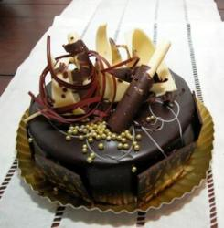 Round chocolate cake with gold beads and white chocolate shavings.JPG