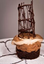 Chocolate dessert cake with tower topping and cream and powdered sugar.JPG