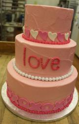 3 tier round pink cake with the word love on middle tier and xoxo on bottom tier.JPG