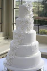 5 tier round white wedding cake with white flowers draping down.JPG