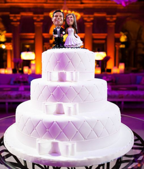Three tier round wedding cake with bowties on each tier and bobblehead groom and bride toppers.JPG