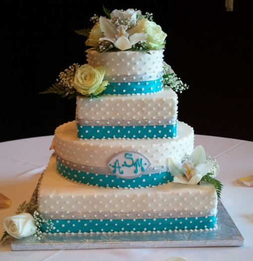 Picture of four tier white + blue wedding cake w/ white dots + yellow