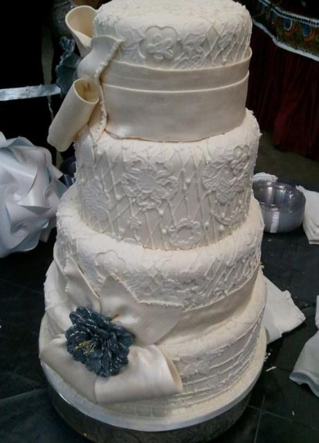 Four tier white round wedding cake with patterns and texture and white bows.JPG