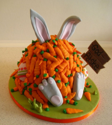 Humor easter cake with bunny covered with carrots holding a sign saying Happy Easter in Danish.PNG
