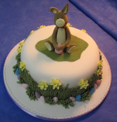 Professional easter cake with grass and easter flowers and bunny cake topper.PNG