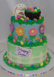 Three tiers with colorful flowers with bunny cake toppers holding the easter eggs and easter egg basket.PNG