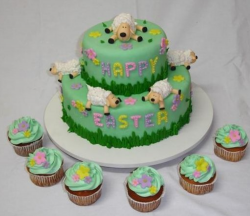 Two tiers easter cake with sheep laying arond and easter cupcakes.PNG