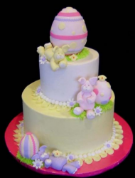 Two tiers easter cakes with gaint easter egg cake topper and yellow bunny.PNG