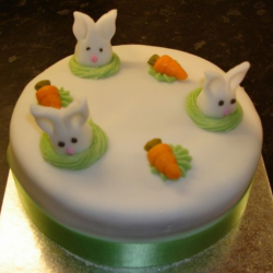 White waster cake with easter bunnies sticking their heads up with carrots.PNG