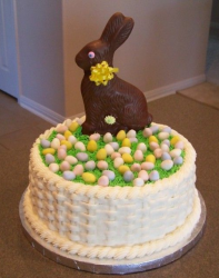 Basket patterns cakes with chocolate bunny cake topper with full of small candy easter eggs.PNG