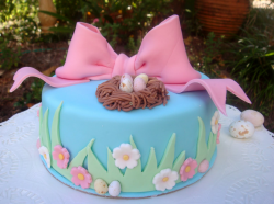 Blue Easter cake with grass and flowers cake decor and big pink bow.PNG