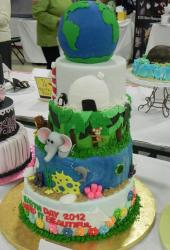 4 tier Earth Day cake with animals and globe of Earth on top.JPG