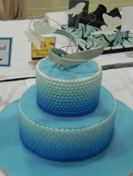 Two tier aqua theme round cake with pearl beads and butterfly sculpture on top.JPG