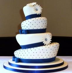 Topsy turvy 4 tier wedding cake with blue bands with bows.JPG
