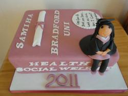 Pink graduation cake with student sitting on textbook.JPG