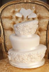 3 tier topsy turvy ivory wedding cake with hearts on top.JPG