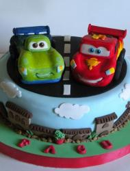 Light blue 1-tier Cars cake with Lightning McQueen and another car on top.JPG