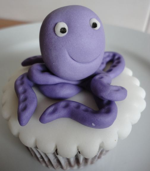 Chocolate cup cake with purple octopus on top.JPG