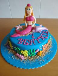 Blue round birthday cake with mermaid and dolphin on top.JPG