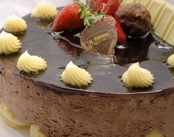 Round chocolate cake with white chocolate bar and fresh strawberries on top.JPG