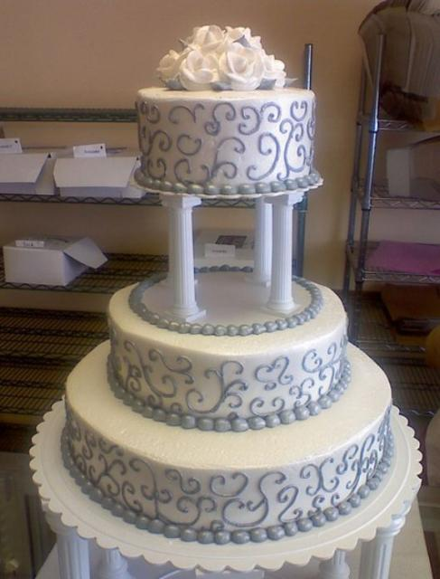 3 Tier Round Wedding Cake With 4 Roman Columns Supporting Third Tier Plus White Roses On TopJPG