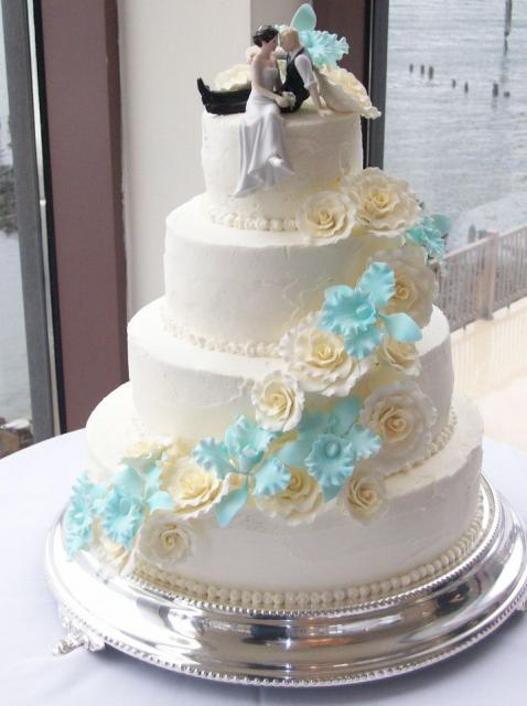 4 Tier White Round Wedding Cake With Cascading Flowers And Bride And Groom Figurine TopperJPG