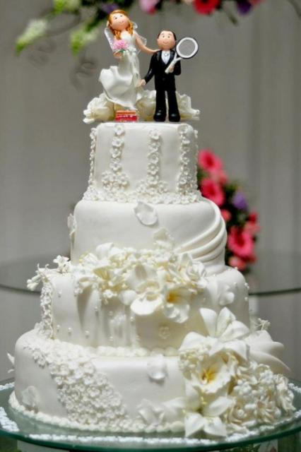 4 tier white wedding cake with bride topper and groom topper holding tennis raquet.JPG