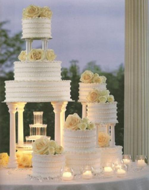 3 Tier Round White Wedding Cake With Roman Columns With Accompanying Smaller CakesJPG