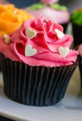 Chocolate cupcake with pink cream and white hearts.JPG
