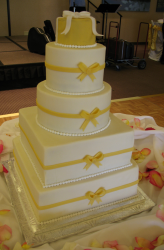 Fancy wedding cake with square and round tiers with pearl patterns decor and yellow ribbon patterns.PNG
