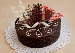 Round mini-chocolate cake with white and dark chocolate slices on top.JPG