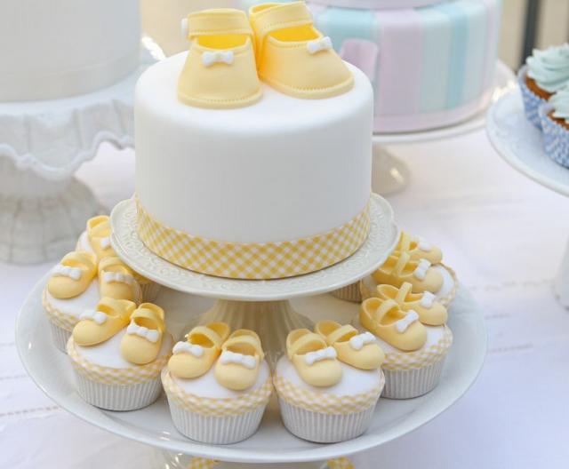 Round white baby shower cake with yellow baby shoes and matching ...